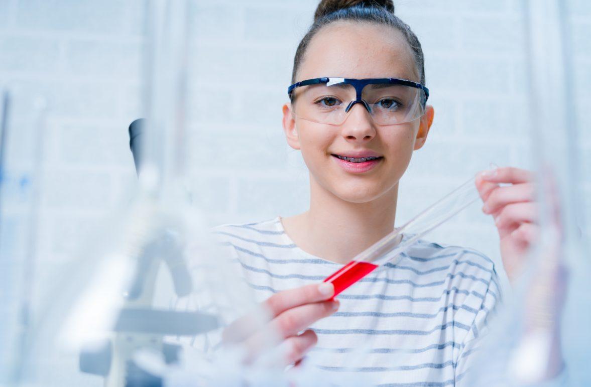 Junge Forscherin mit Reagenzglas
